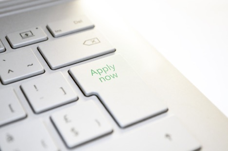 white laptop keyboard focus on apply now button in green