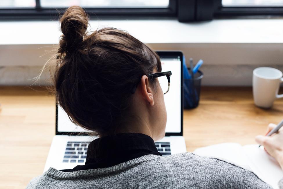 back of women's head in front of open laptop on a desk.