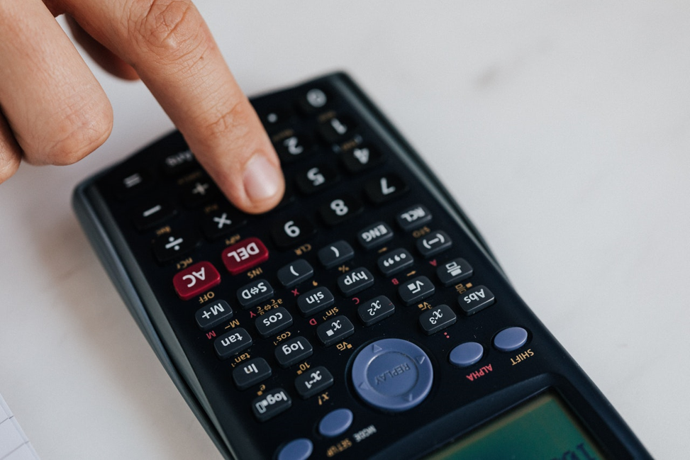 person punching in their budget percentages into their calculator.