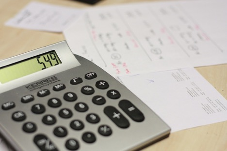 grey calculator with black and white buttons showing 549 on a table with papers.
