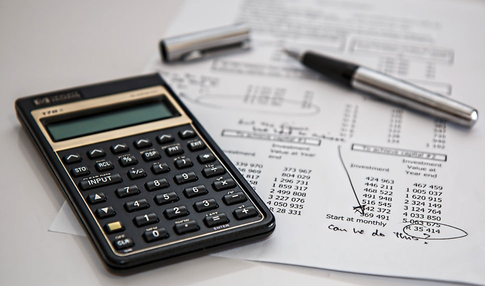 Balance sheet with a calculator and pen