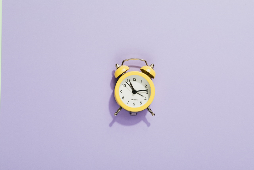 Analog alarm clock in front of purple background.