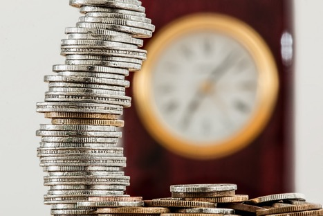 stack of coins and clock in the background