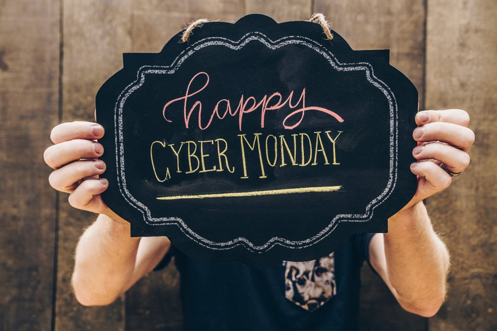Person in black t-shirt standing in front of wooden slats holding stylized blackboard showing happy cyber Monday