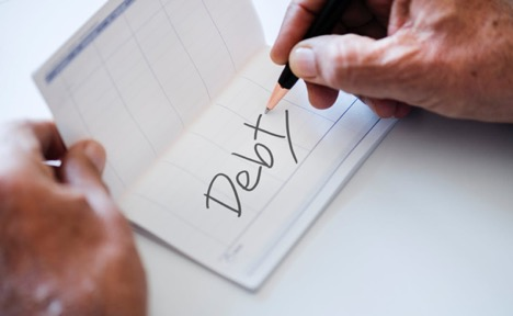 man holding open a chequebook that says debt in left hand and a pen in his right hand