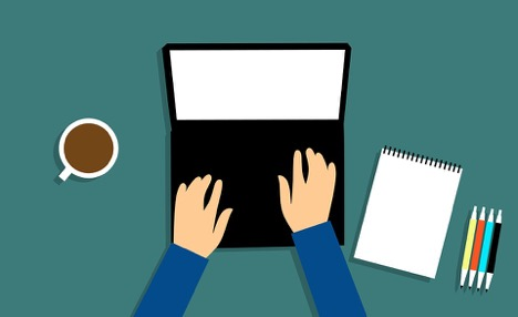 man with blue sleeves typing on open laptop next to a coffee note pad and four pens
