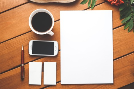 white page next to coffee mug phone two notepads and pen on wooden surface