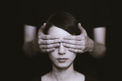 person covering another person's eyes with their hands in a black background