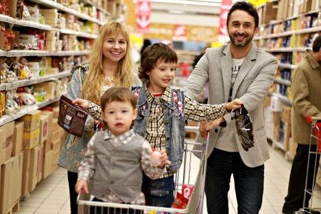 Family of four doing groceries with a shopping cart