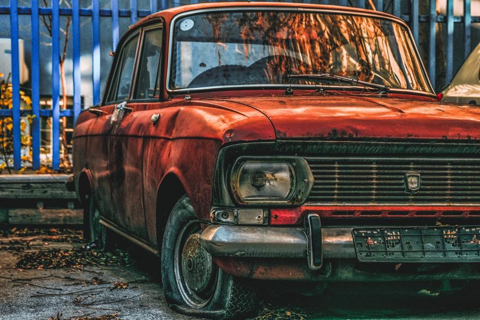 Rusty orange car with a flat tire.