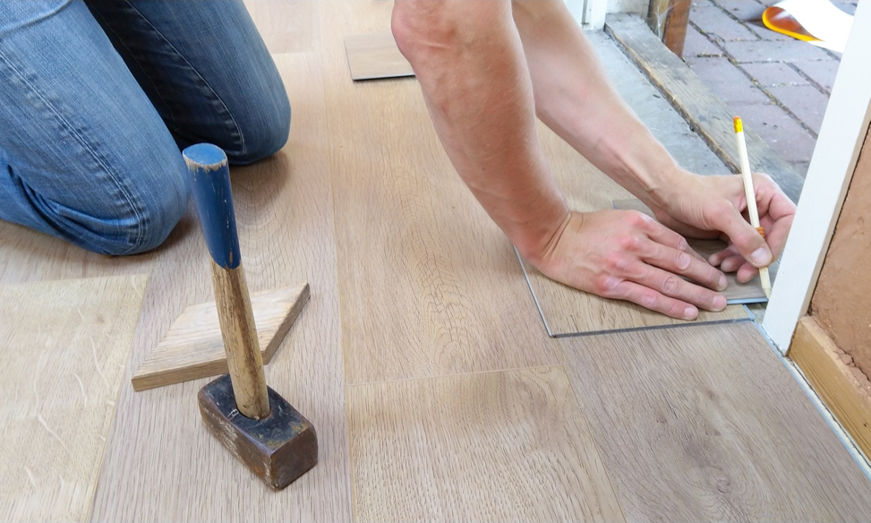 Person installing new flooring.