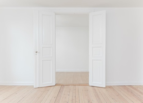 white double doors in a white room with wooden floors open to show another white room