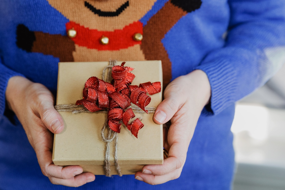 man wearing blue sweater with reindeer pattern and holding cardboard box with red ribbon and twine