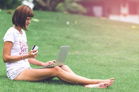Woman sitting on grass holding credit card and looking at her computer