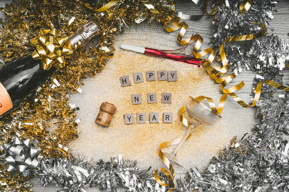 Happy New Year in scrabble tiles covered in gold glitter next to champagne glass champagne bottle cork bows streamers and tinsel