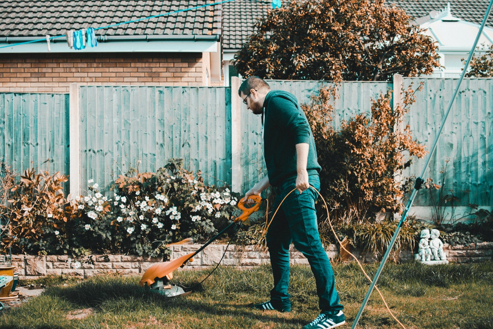 Person cutting lawns to save their money.