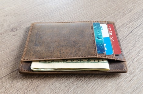 wallet on a table with American money and credit cards in it