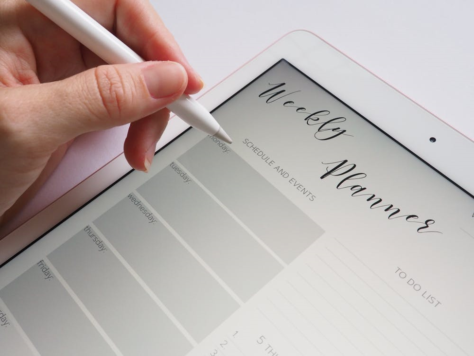 left hand holding white stylus to iPad screen showing weekly planner schedule events and to do list