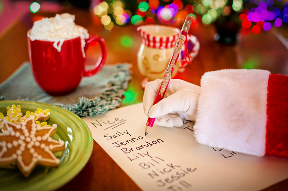 Santa holding pencil in right hand over naughty and nice list next to plate of Christmas cookie and mug with whipped cream topping
