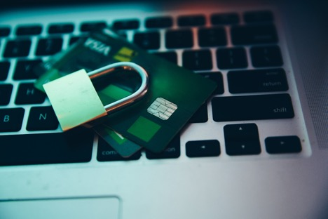 padlock on two credit cards on top of laptop keyboard