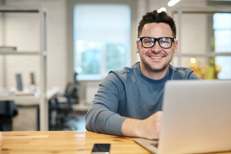 smiling man in black glasses sitting at wooden desk next to open laptop researching an online flex loan