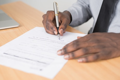 man in tie signing document on desk with right hand