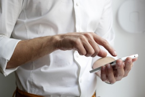 man in white button-down shirt holding white phone in left hand and pointing at the screen with his right hand in a white room