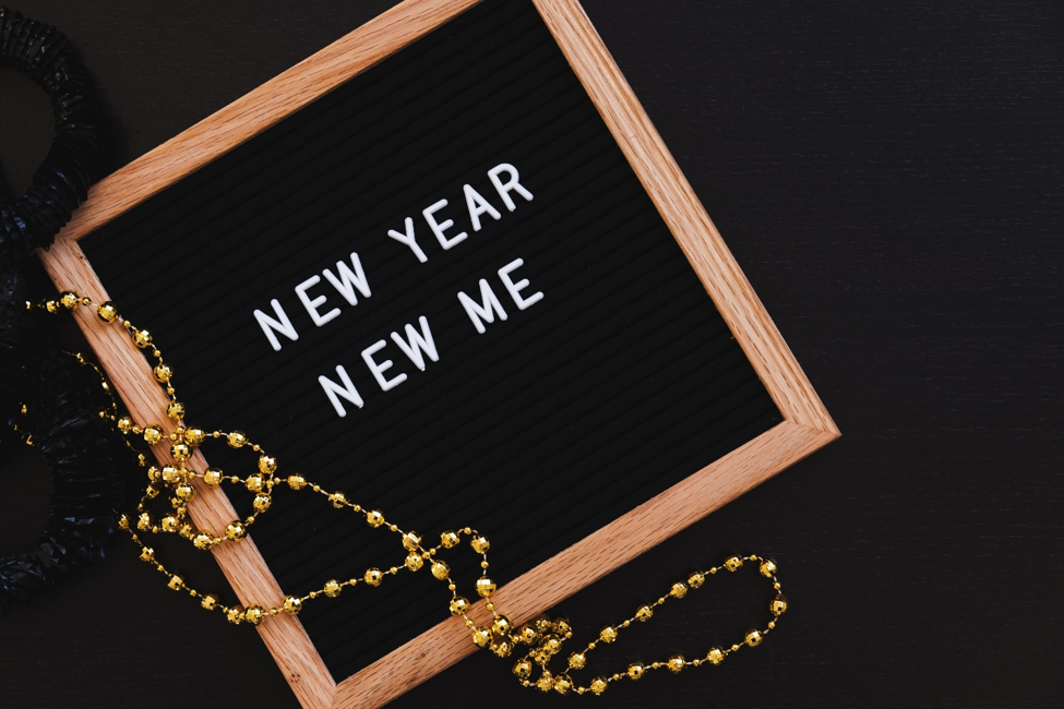 New Year New Me in white lettering on black board with wooden frame next to black and gold beads on black background