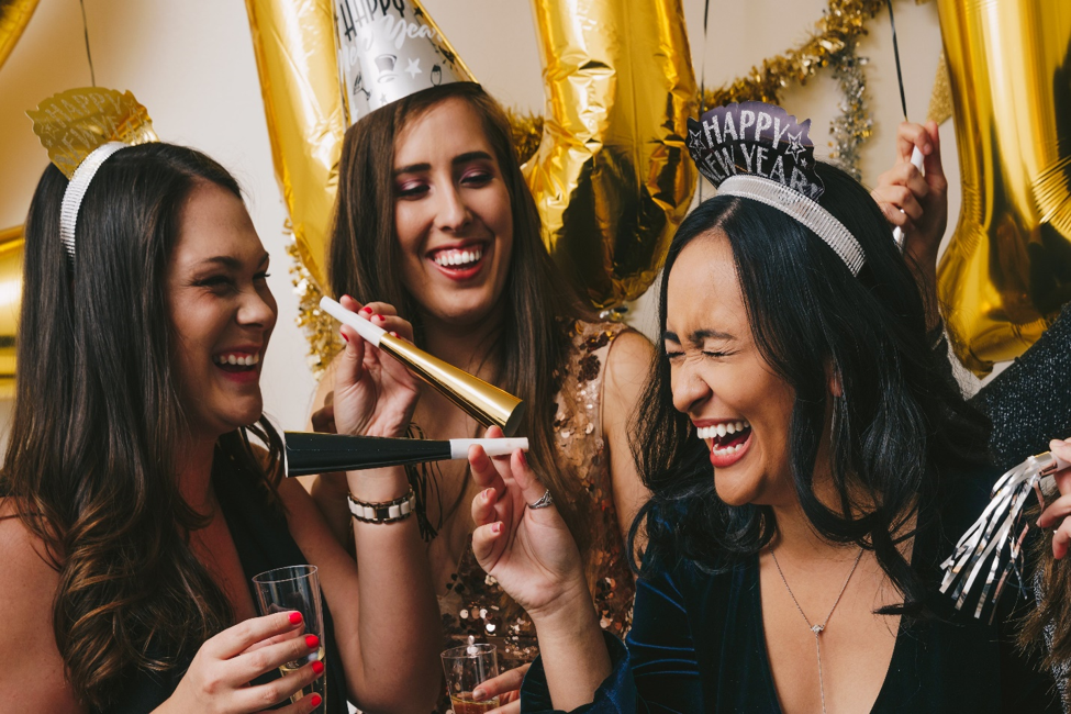 three women laughing holding Happy New Year accessories