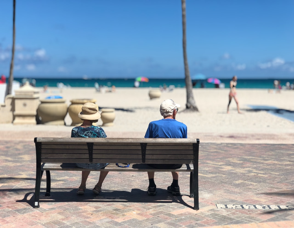 old people sitting on a bench in front of a beach.