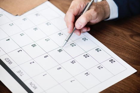 man holding pen in right hand pointing to Tuesday 16 on white calendar on wooden surface
