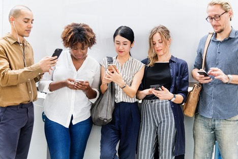 line of young people in casual clothing looking at their phones in front of a blank wall outside