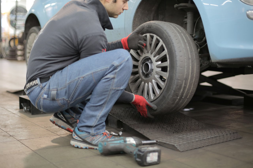 person changing a tire on a blue car.