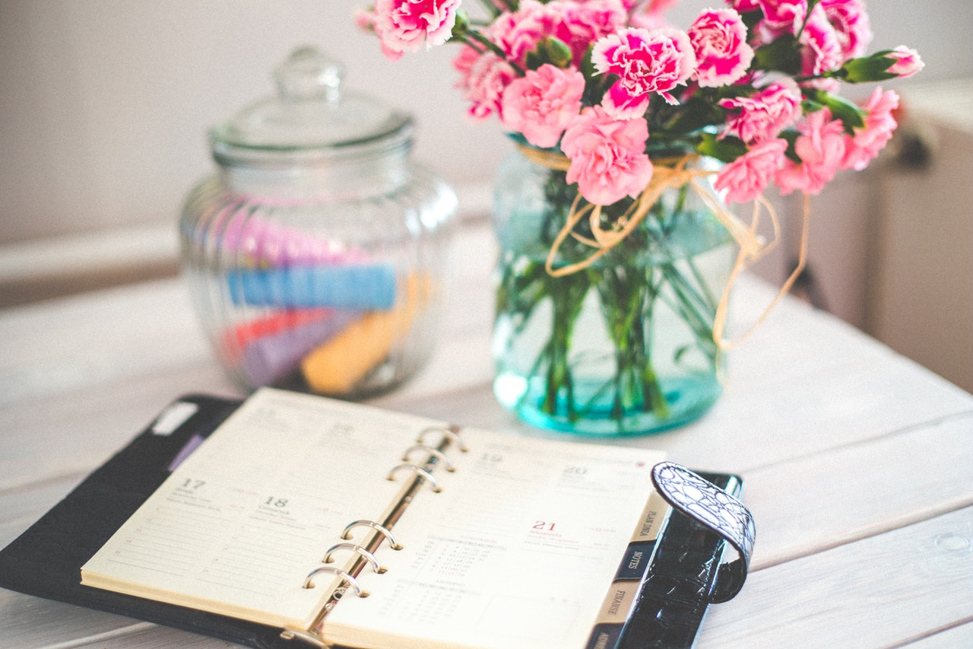 flowers and daily planner open on desk