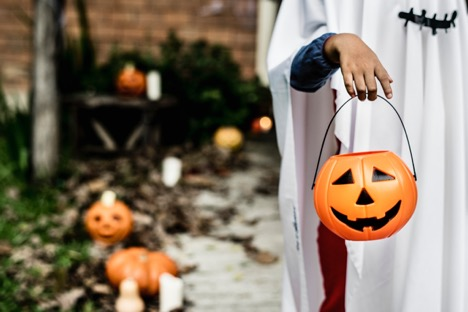 person in white sheet holding pumpkin container in right hand outside
