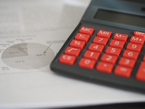 red and black calculator on top of a piece of paper showing a grey-scale pie graph