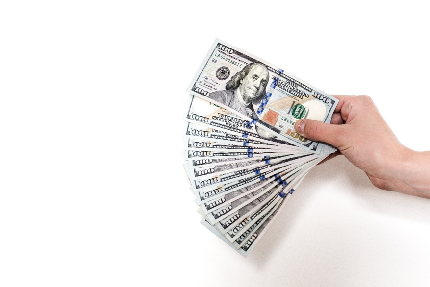 right hand holding multiple $100 American bills received from popular online loans
