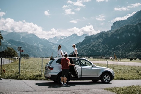 three people standing outside their car looking at mountains
