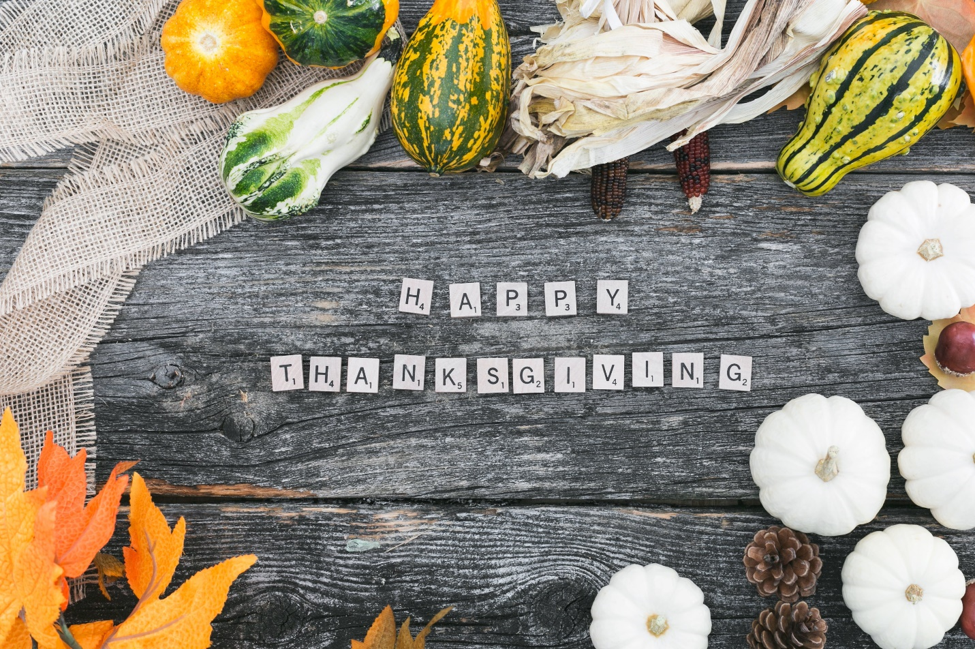 scrabble tiles spelling out happy thanksgiving on wooden planks surrounded by gourds burlap leaves and dried corn