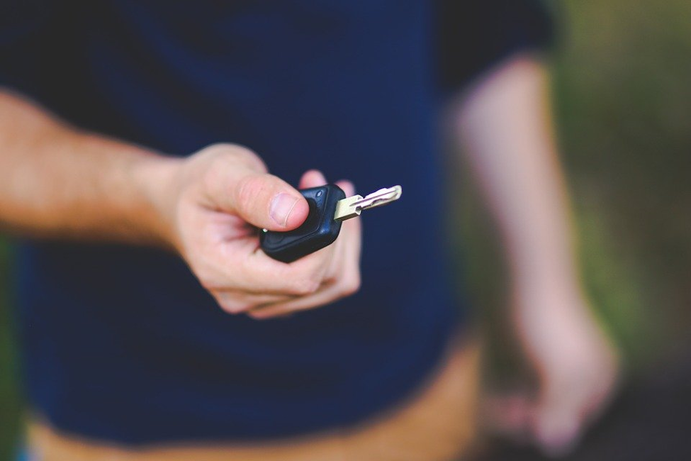 select focus on man's outstretched hand holding car keys