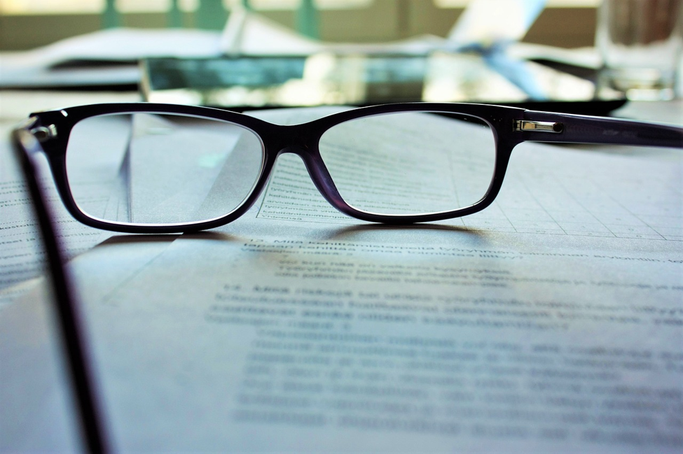select focus on pair of black glasses resting on stack of papers