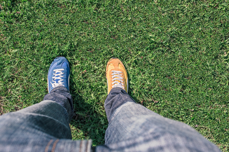 person wearing a blue shoe and an orange shoe.