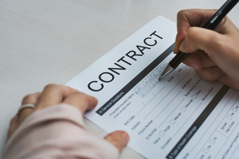 person wearing ring on left hand holding pen in right hand to fill out contract application form