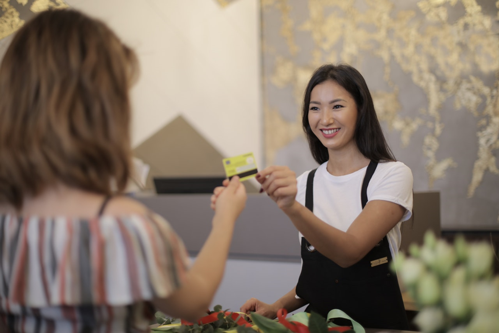 person smiling at handing credit card to another person