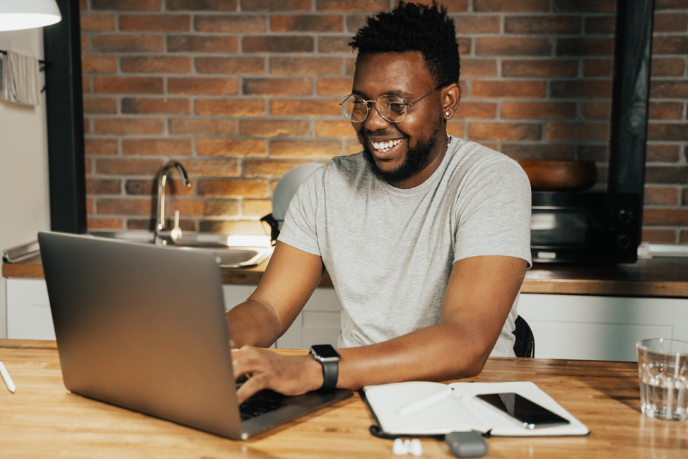 person smiling and researching 401(k) loans on their laptop