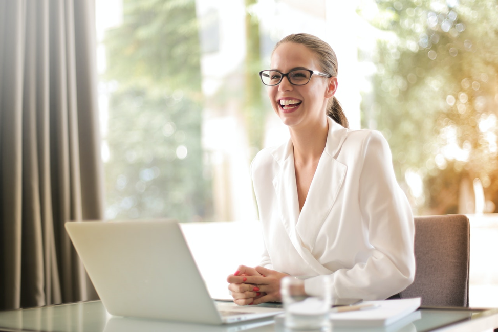 lady smiling at her computer while looking at short term loans online.