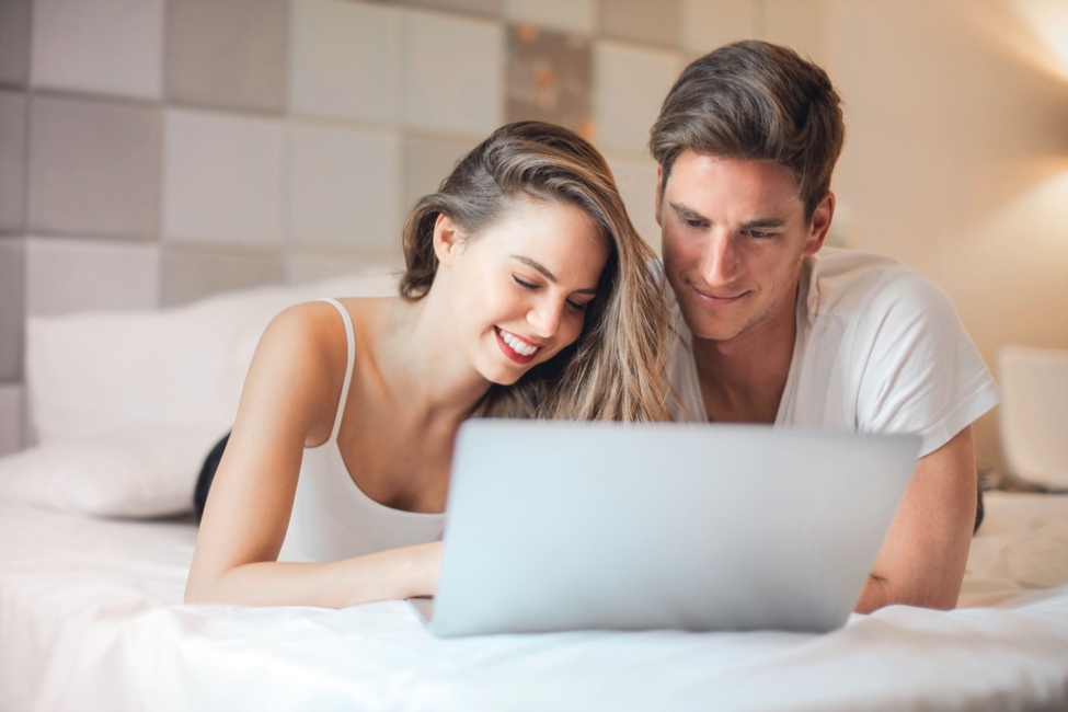 smiling couple lying on white bed in front of open laptop researching unsecured loans online.
