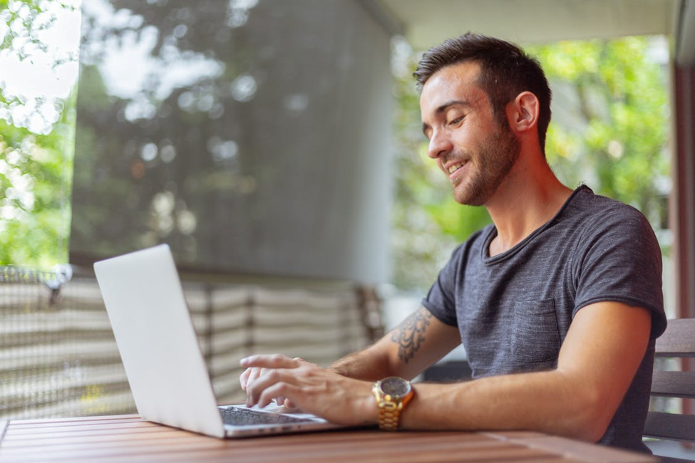 smiling man looking up tips online to help him prepare for the next recession