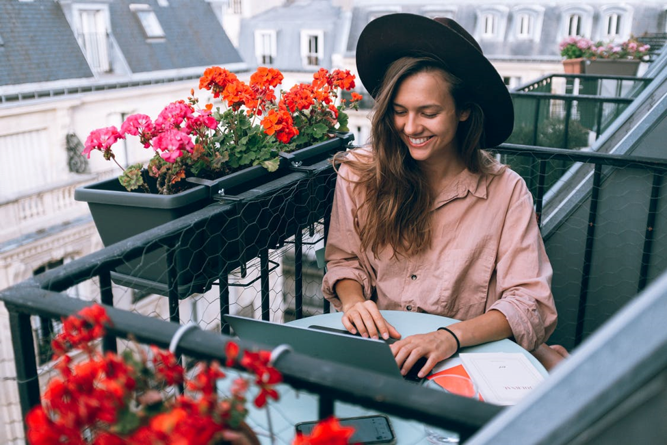 smiling woman in black hat sitting at a table next to open laptop on balcony next to flowers
