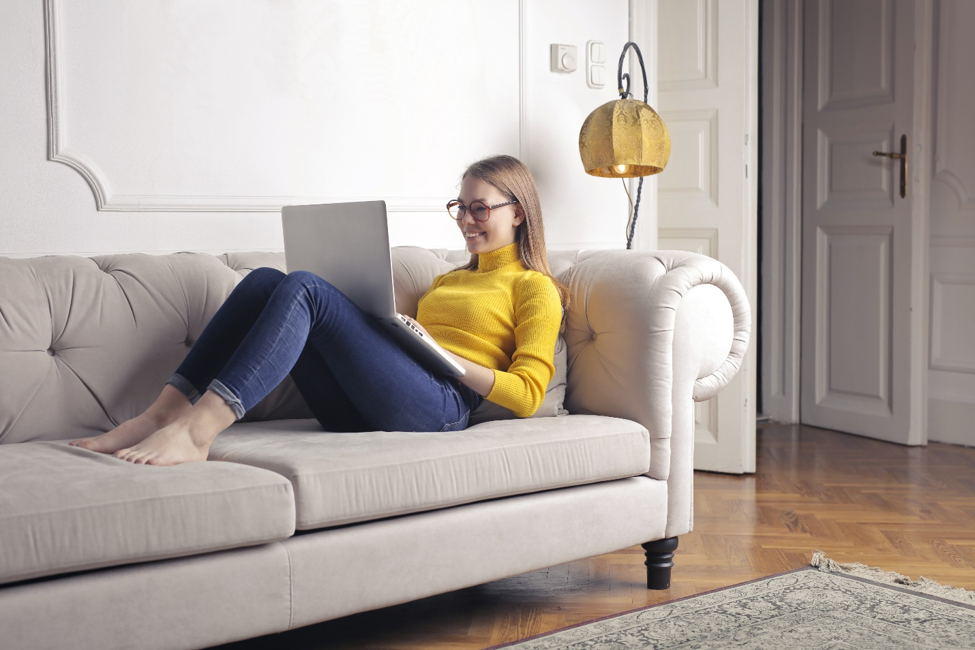 smiling woman in yellow turtleneck reclining on grey couch while resting open laptop on her knees.